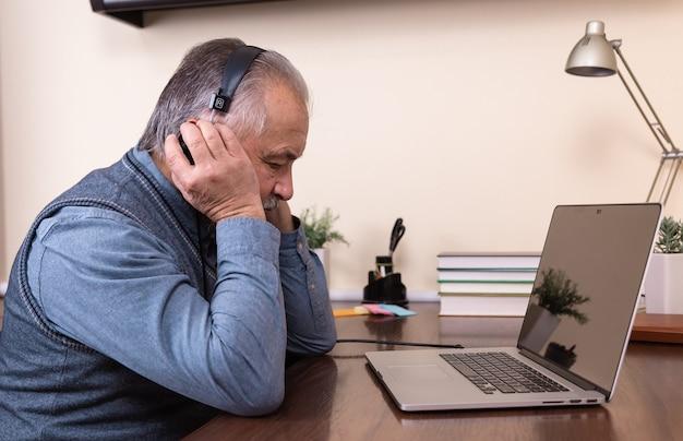 音楽を聴いている年配の男性。ラップトップと自宅でヘッドフォンを身に着けている幸せな老人。アクティブな老後の概念