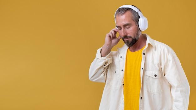 Senior man listening to music through headphones