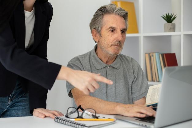 Старший мужчина слушает своего учителя в классе