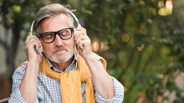 Старший мужчина слушает музыку