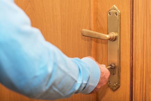 Старший человек запирание двери с ключом в руке