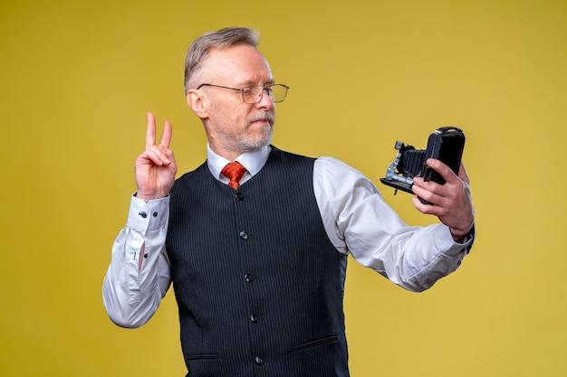 手でカメラを見ている年配の男性。カメラにピースサインを示す自分撮りを撮る男