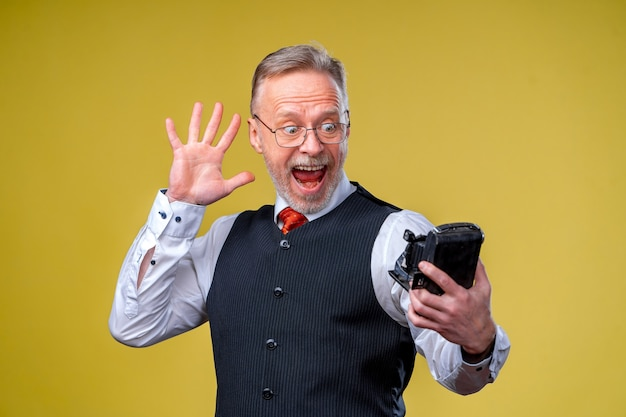 Старший мужчина смотрит в камеру, принимая селфи с глупым лицом, машет в камеру