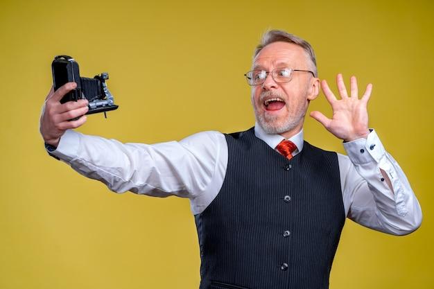 愚かな顔の自撮りをしながらカメラを見ている年配の男性。カメラに手を振る