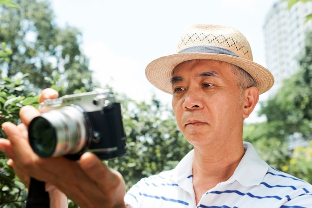Старший мужчина смотрит на экран камеры