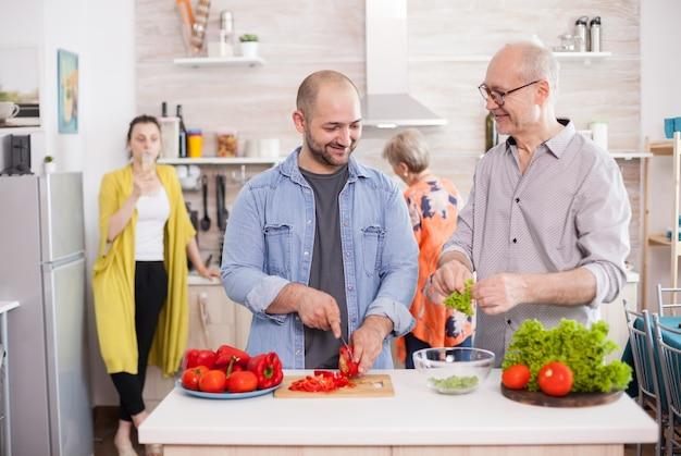 おいしいサラダを準備しながら息子を見ている年配の男性。