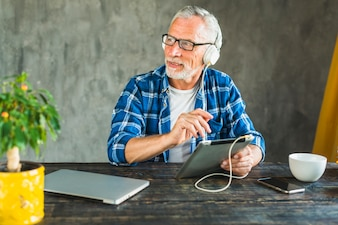 Senior man looking away listening music through headphone on digital tablet