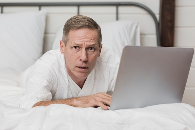 Senior man looking concerned on his laptop in bed