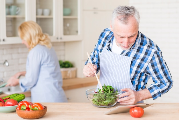 Senior man looking at digital tablet preparing the green salad in the glass bowl and her wife working at background