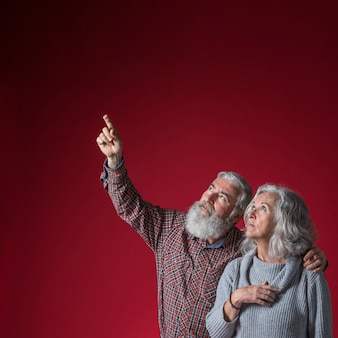 Senior man looking at her husband showing something upward against red background