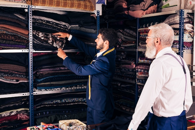 Senior man looking at male tailor taking fabric from shelf in the workshop