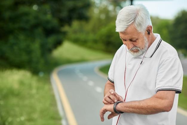 Старший мужчина, глядя на часы во время утренней пробежки.