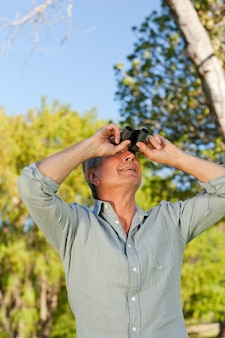Senior man looking at the sky with his binoculars
