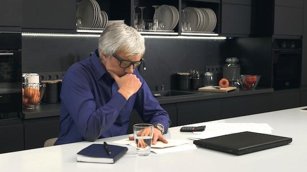 年配の男性が台所で閉じた手紙を見る