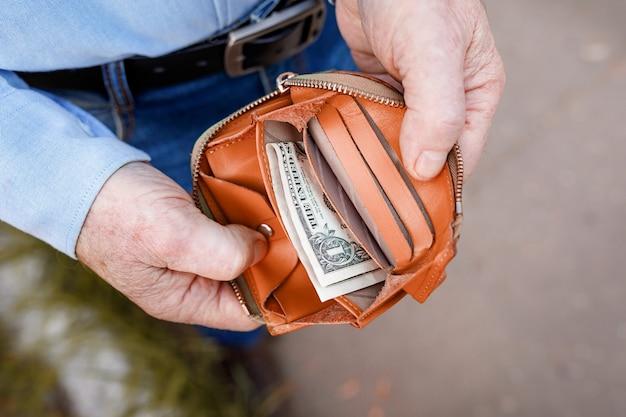 Старший мужчина смотрит в сумочку с одним долларом кошелек с последним долларом в руках пожилого мужчины