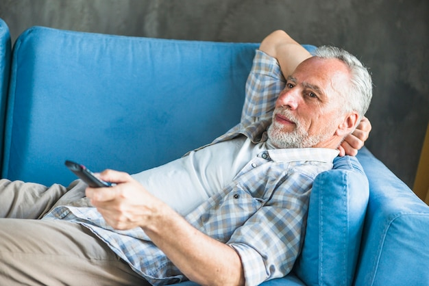 Senior man lying on blue sofa using remote control