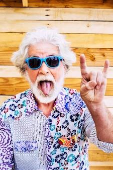 웃긴 표정을 짓고 나무 벽에 몸짓을 하는 수석 남자. 펑키 셔츠와 선글라스를 쓴 노인 초상화. 손으로 몸짓을 하고 유머러스한 얼굴을 하는 노인