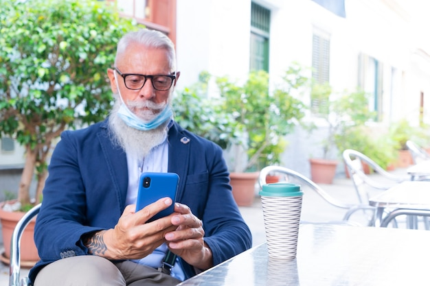 Senior man in mask with modern phone sitting in cafe during coronavirus outbreak, new normal concept