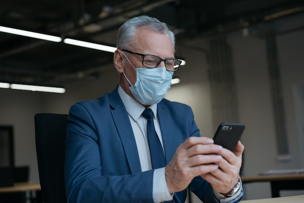 Senior man in medical mask using mobile phone working from home.  social distance concept