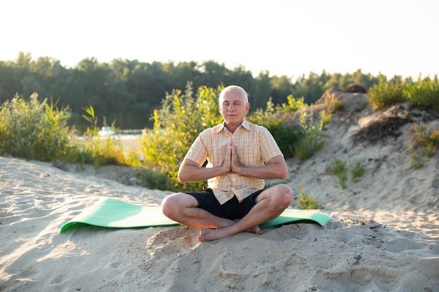 Senior man meditating in beach, sitting lotus pose on yoga mat, zen
