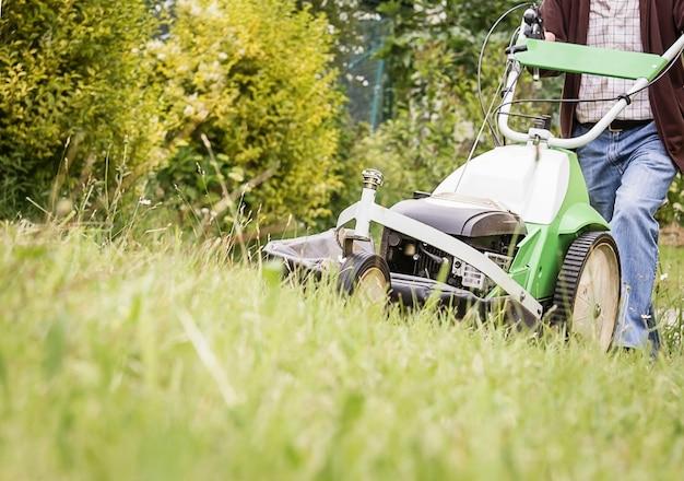 잔디 깎는 기계로 잔디를 깎는 노인