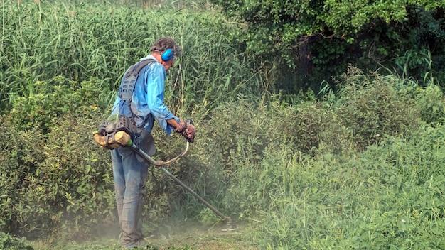 年配の男性がガソリンブラシカッターで草を刈っています。作業服、防音イヤーマフ、手袋、保護メガネを着用している男性