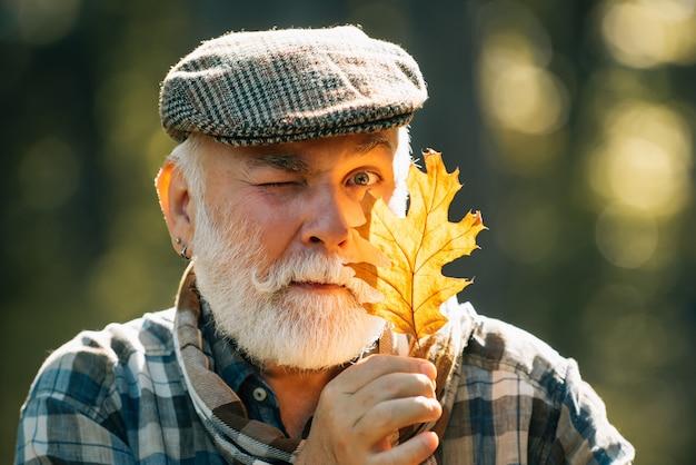 Старший мужчина на прогулке в лесу в осенней природе, держащей листья. grangfather гуляет в парке на желтых осенних листьях.