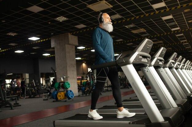 Старший мужчина на беговой дорожке в тренажерном зале