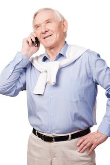 電話の年配の男性。白い背景に立っている間カメラで笑って幸せな年配の男性の肖像画
