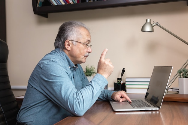Senior man online communication. old man makes videocall talking with relatives or friends by video conference app