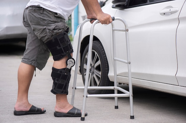 Senior man opens the car door with a walker on the road