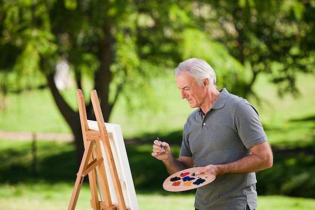 Senior man painting in the garden