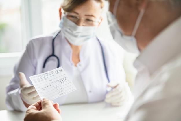 Covid-19ワクチン接種記録カードを読んでいる診療所の年配の男性患者。医者は老人に予防接種について説明します