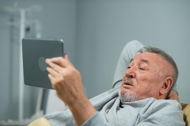Старший мужчина, пациент, держащий цифровой планшет в руке и смотрящий фильм, лежа в постели в больничной палате, здоровая сильная медицинская концепция.