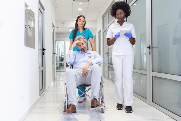 Senior man patient in wheelchair sitting in hospital corridor with doctor and nurse