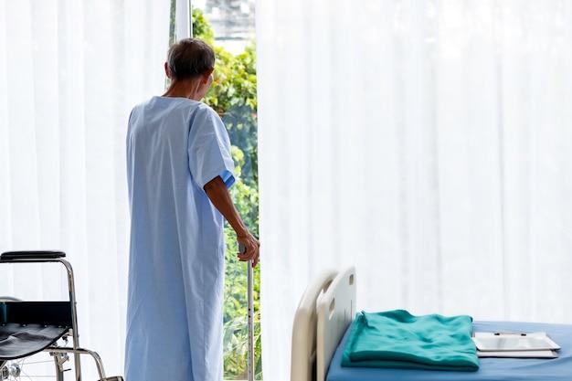 病室で杖を持つシニア男性患者。