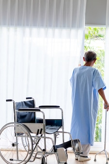 Пациент старшего человека с тростью в палате.