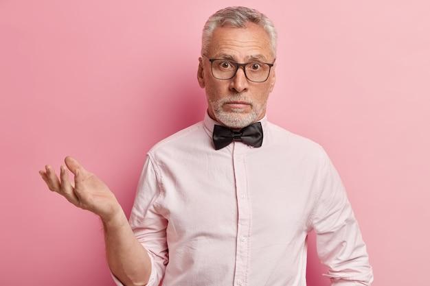 Uomo anziano in camicia rosa e papillon nero
