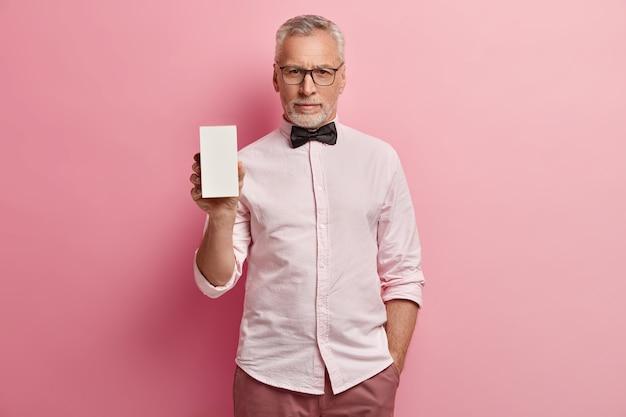 Senior man in pink shirt and black bowtie