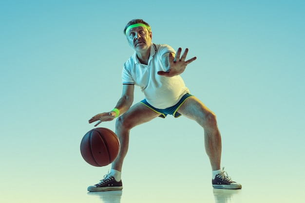 Senior man playing basketball on gradient wall in neon light. caucasian male model in great shape stays active, sportive. concept of sport, activity, movement, wellbeing, healthy lifestyle.