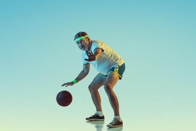 Uomo anziano che gioca a basket sulla parete sfumata in luce al neon