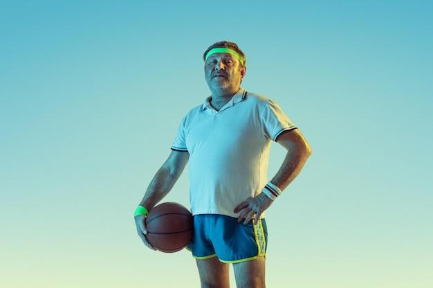 ネオンの光のグラデーションの背景でバスケットボールをしている年配の男性。素晴らしい形の白人男性モデルは、アクティブでスポーティーなままです。