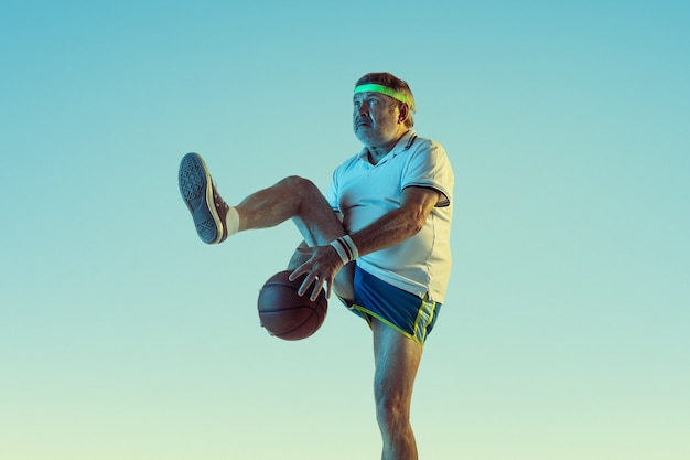 Старший мужчина играет в баскетбол на стене градиента в неоновом свете. кавказский мужчина-модель в отличной форме остается активным, спортивным. понятие спорта, активности, движения, благополучия, здорового образа жизни.