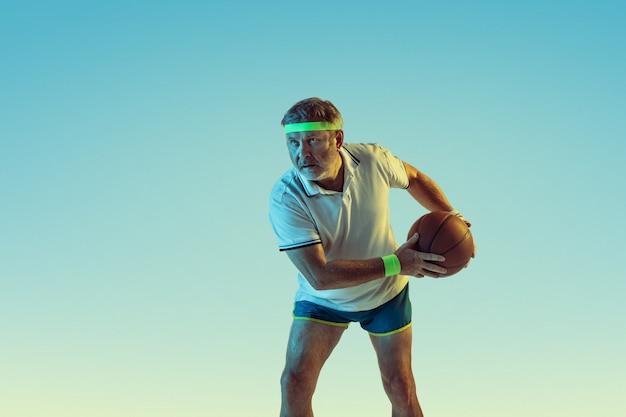 Старший мужчина играет в баскетбол на градиентной стене в неоновом свете