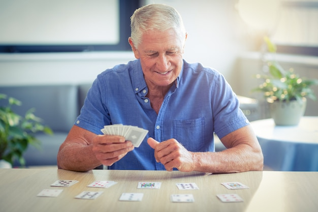 Senior man playing cards in living room