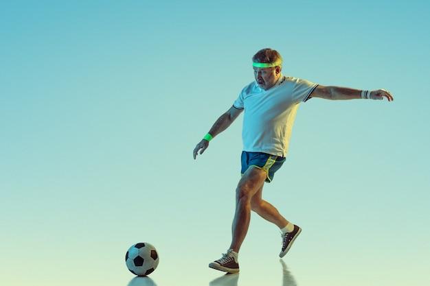 Старший мужчина играет в футбол в спортивной одежде на градиенте и неоновом свете