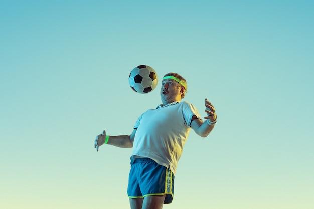 Uomo anziano che gioca a calcio in abbigliamento sportivo su gradiente e luce al neon