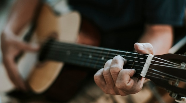 彼のギターで遊んでいる年配の男性