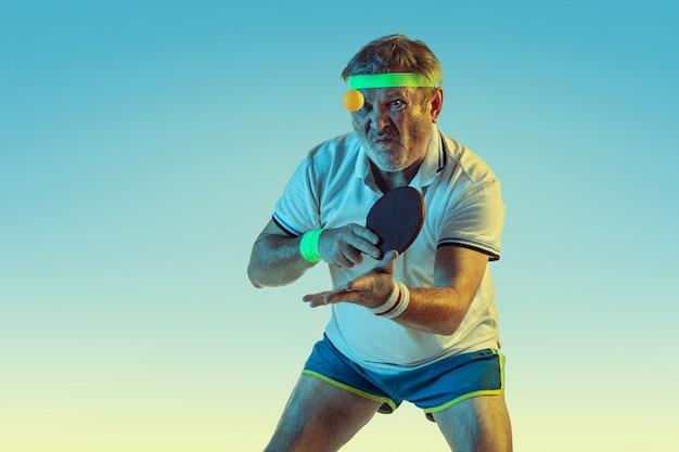 Uomo maggiore che gioca a ping-pong sulla parete di pendenza nella luce al neon