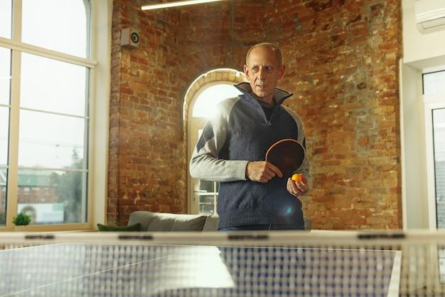 Старший мужчина играет в настольный теннис на рабочем месте с удовольствием мужская модель играет в пинг-понг